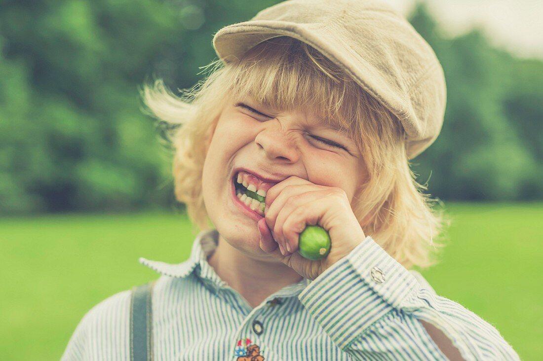 A blond boy wearing a hat biting into a cucumber
