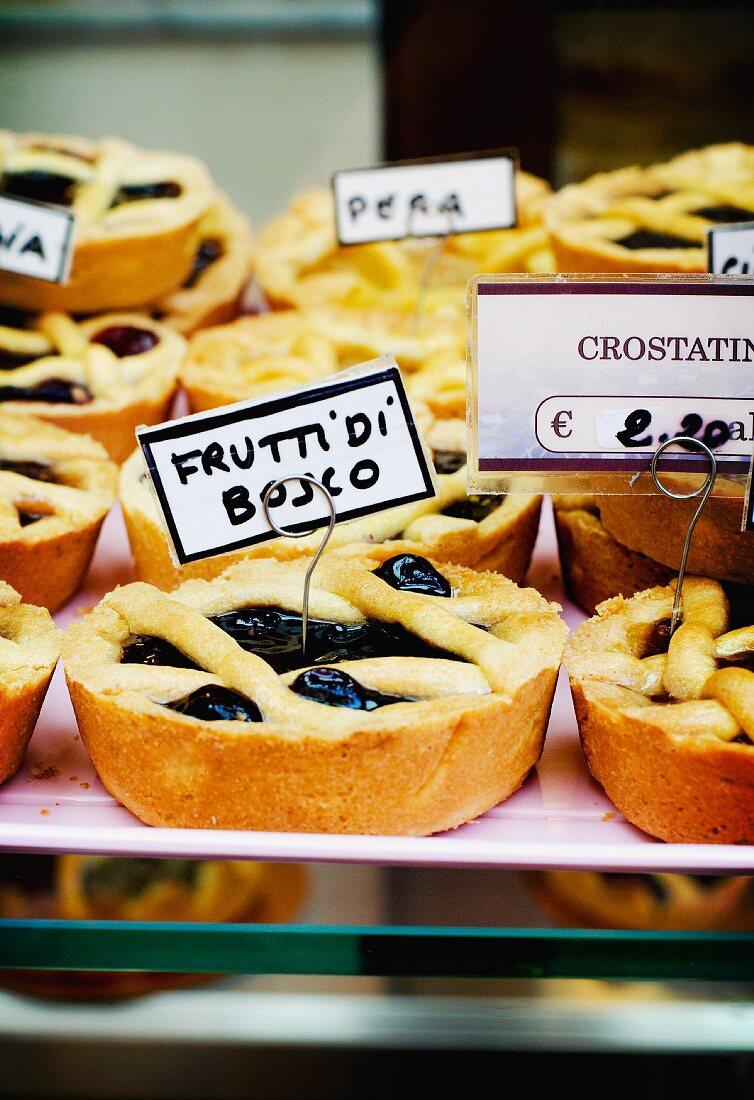 Frutti di bosco (forest fruits) tartlets on display in an Italian bakery