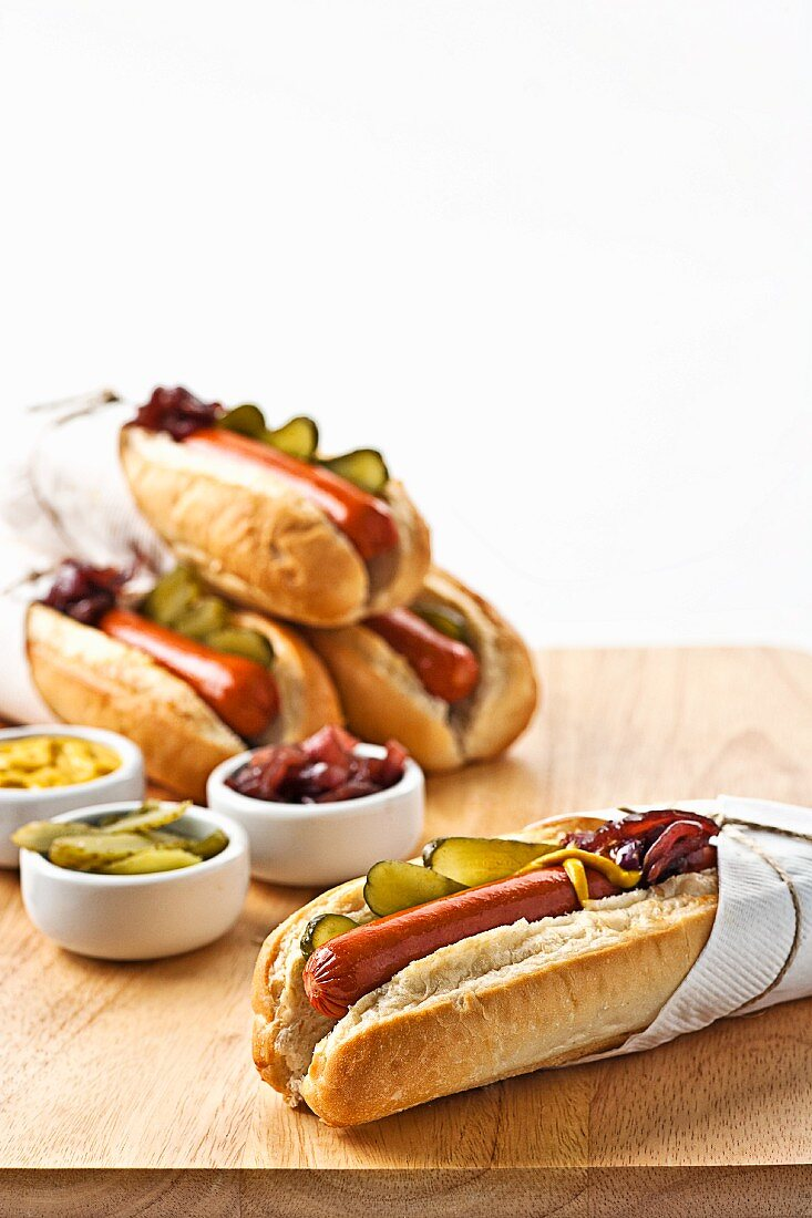Hot dogs in rolls with gherkins, mustard and relish