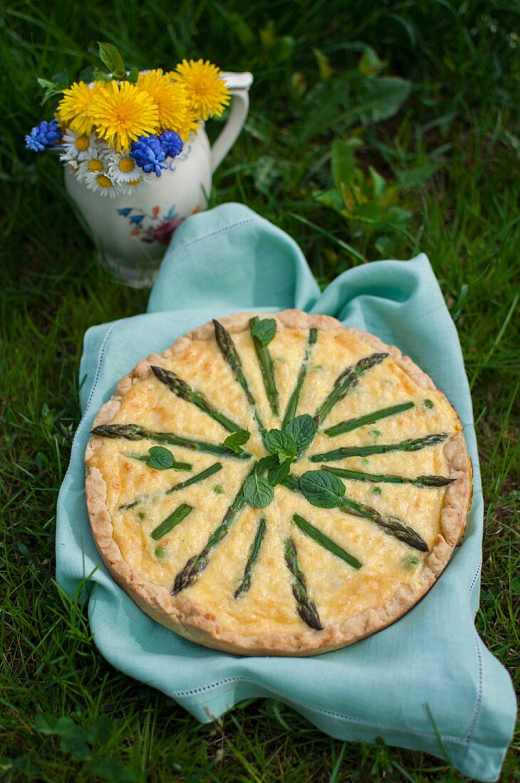 Quiche with asparagus, peas and fresh mint in a garden
