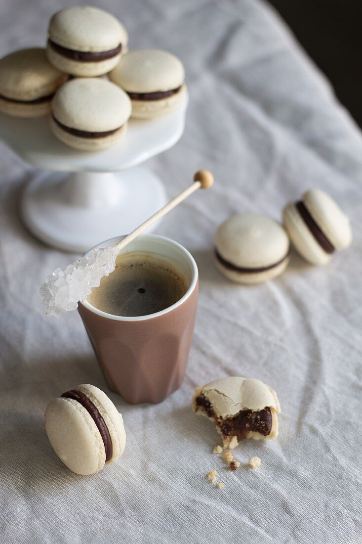 Macaroons and coffee with a stick of rock sugar