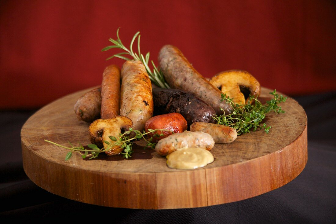 A wooden platter with various cooked sausages, herbs, mushrooms and mustard