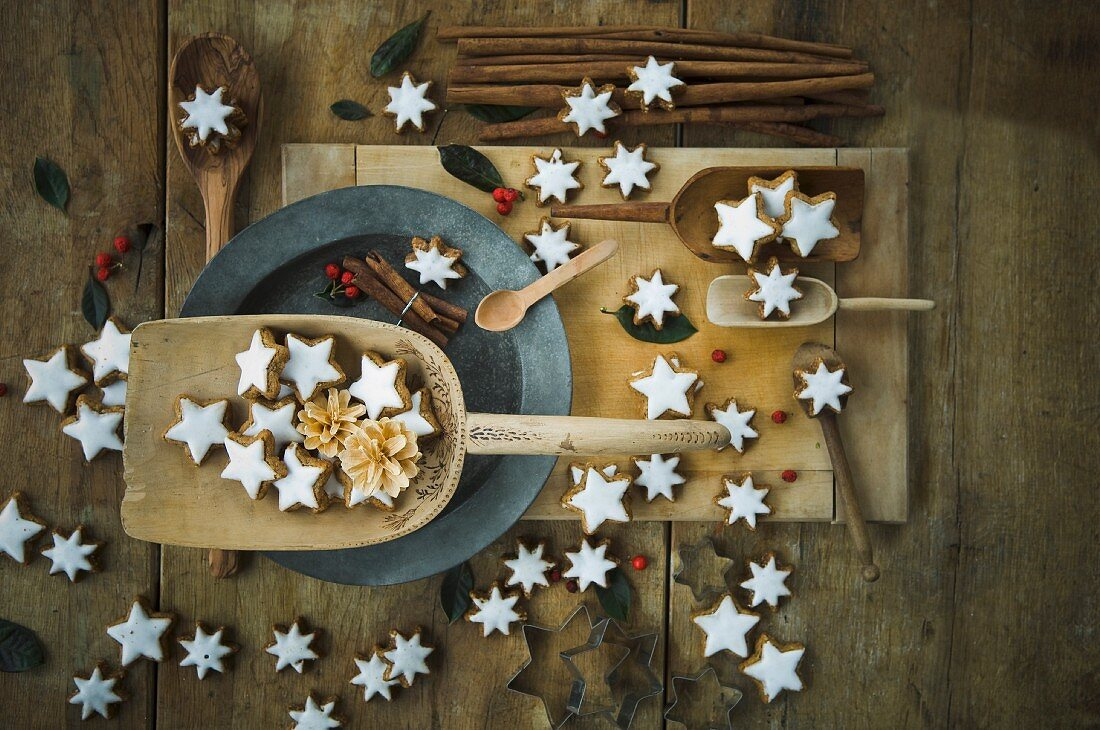 An arrangement of cinnamon star biscuits, wooden spoons, cinnamon sticks and cutters
