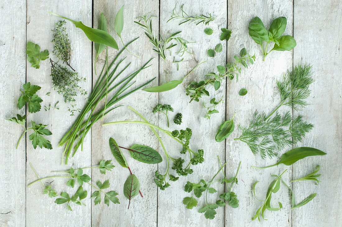 Lots of different fresh kitchen herbs on a wooden surface (seen from above)