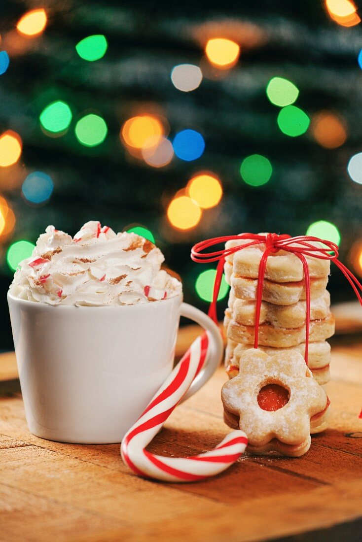 A cappuccino with cream, a candy cane and a stack of biscuits