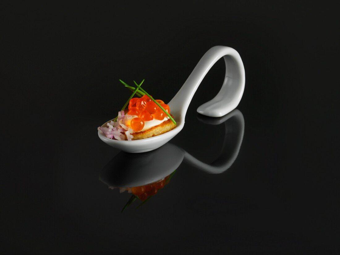 A buckwheat blini and keta caviar on a tasting spoon