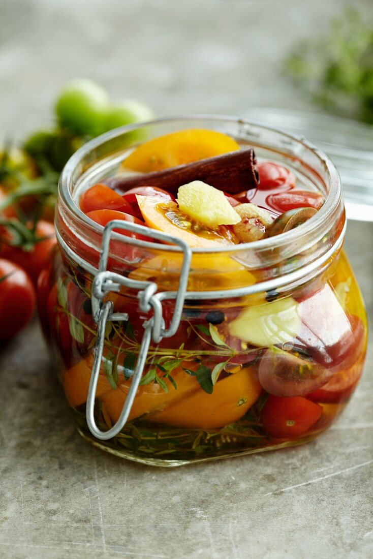 Pickled tomatoes with herbs and cinnamon in a preserving jar
