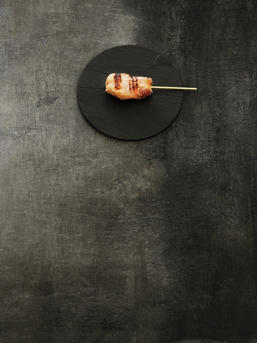 Grilled meat kushi on a black stone platter