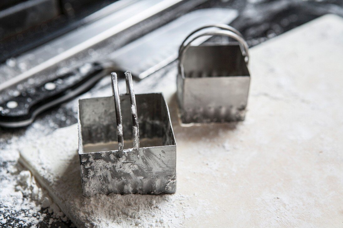 Two square pastry cutters on a floured sheet of pastry