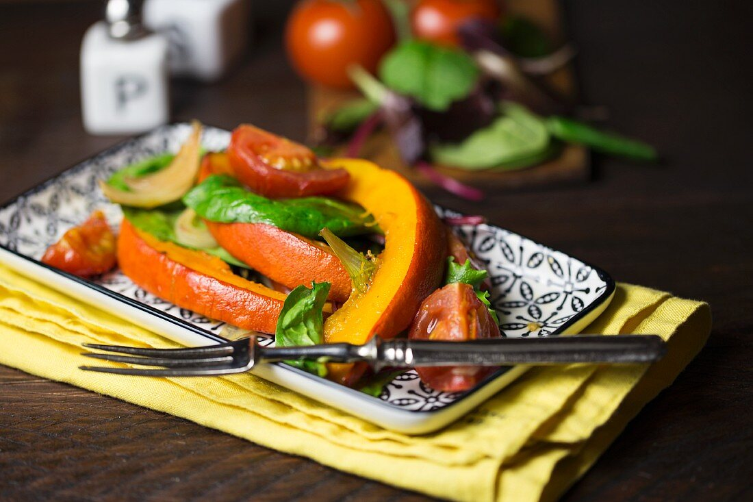 Oven-roasted pumpkin on a mixed leaf salad with tomatoes and onions