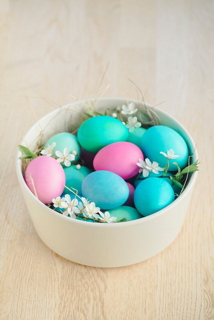 Coloured Easter eggs with flowers and straw in a bowl