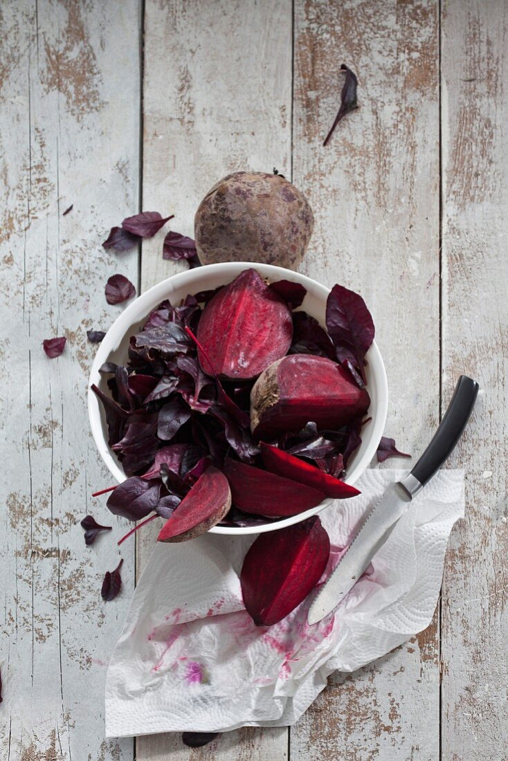 Fresh beetroot and beetroot leaves on a wooden surface (seen from above)