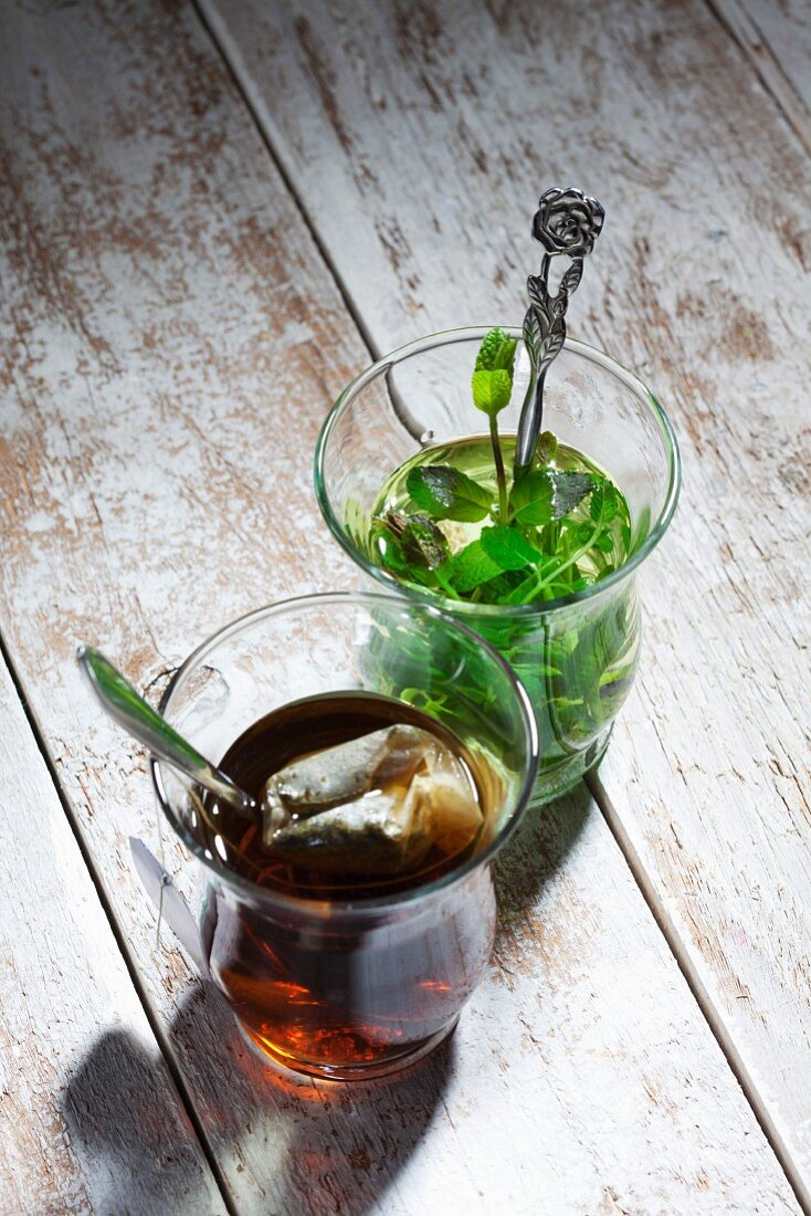 Two glasses of mint tea one with a teabag and one with fresh mint