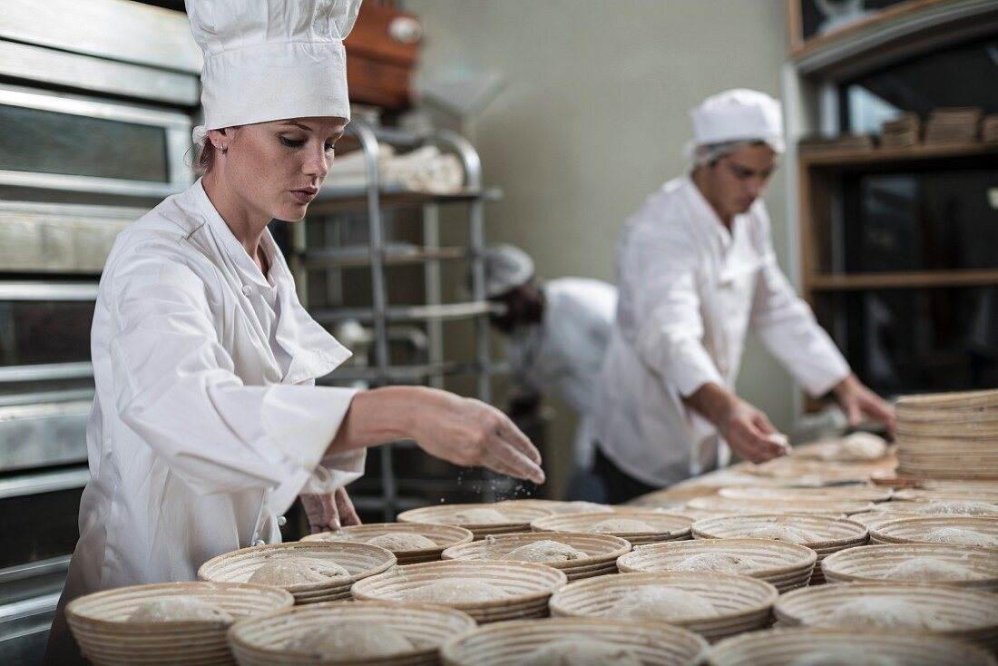 Bakers making bread: dough being dusted with flour in baking baskets