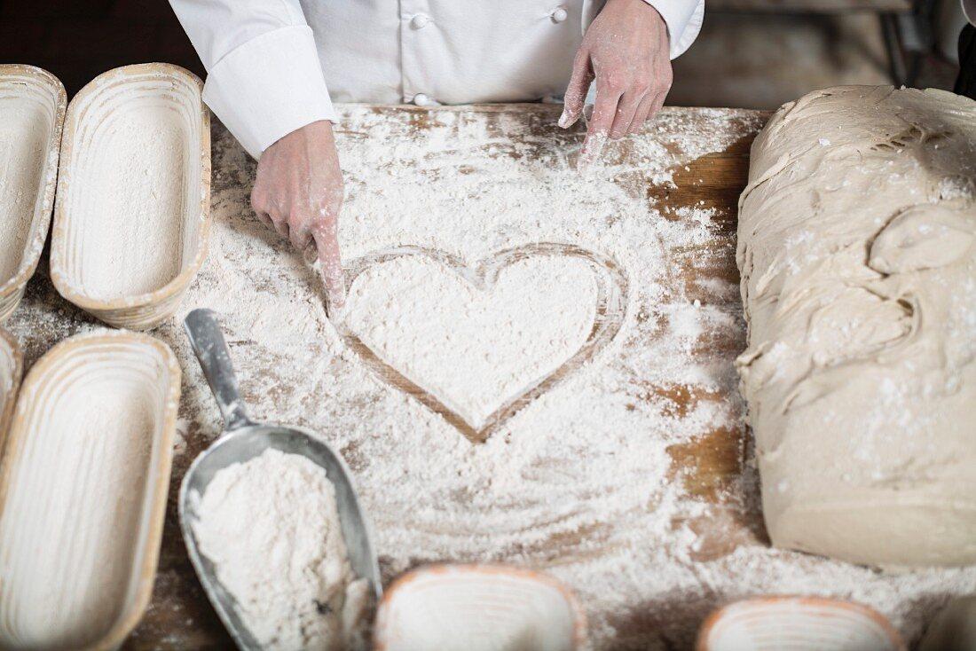 A baker drawing a heart on a floured work surface between baking baskets and dough