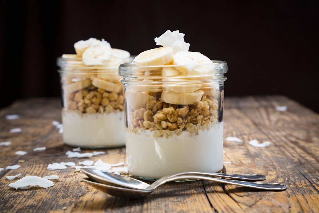 Crispy muesli with natural yoghurt, bananas and coconut chips in glasses