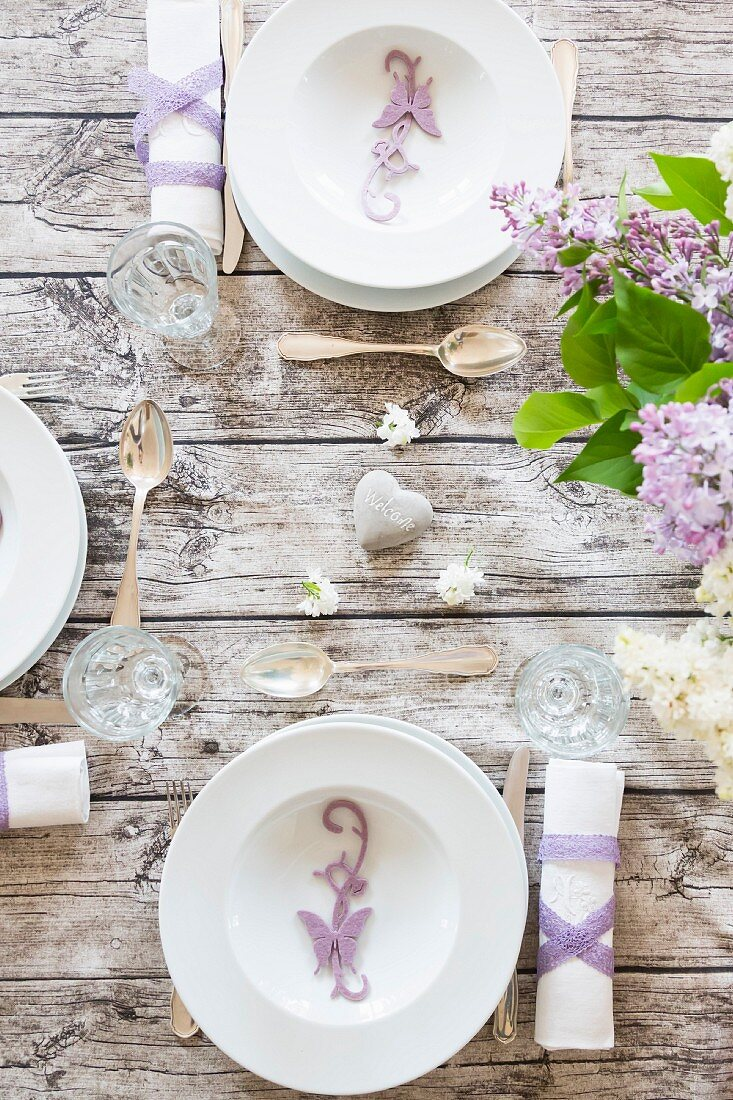 Spring dining table festively set with bouquet of lilac & butterfly ornaments