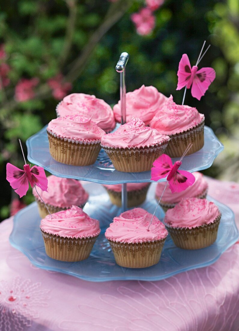 Cupcakes with rose cream on a cake stand on a garden table