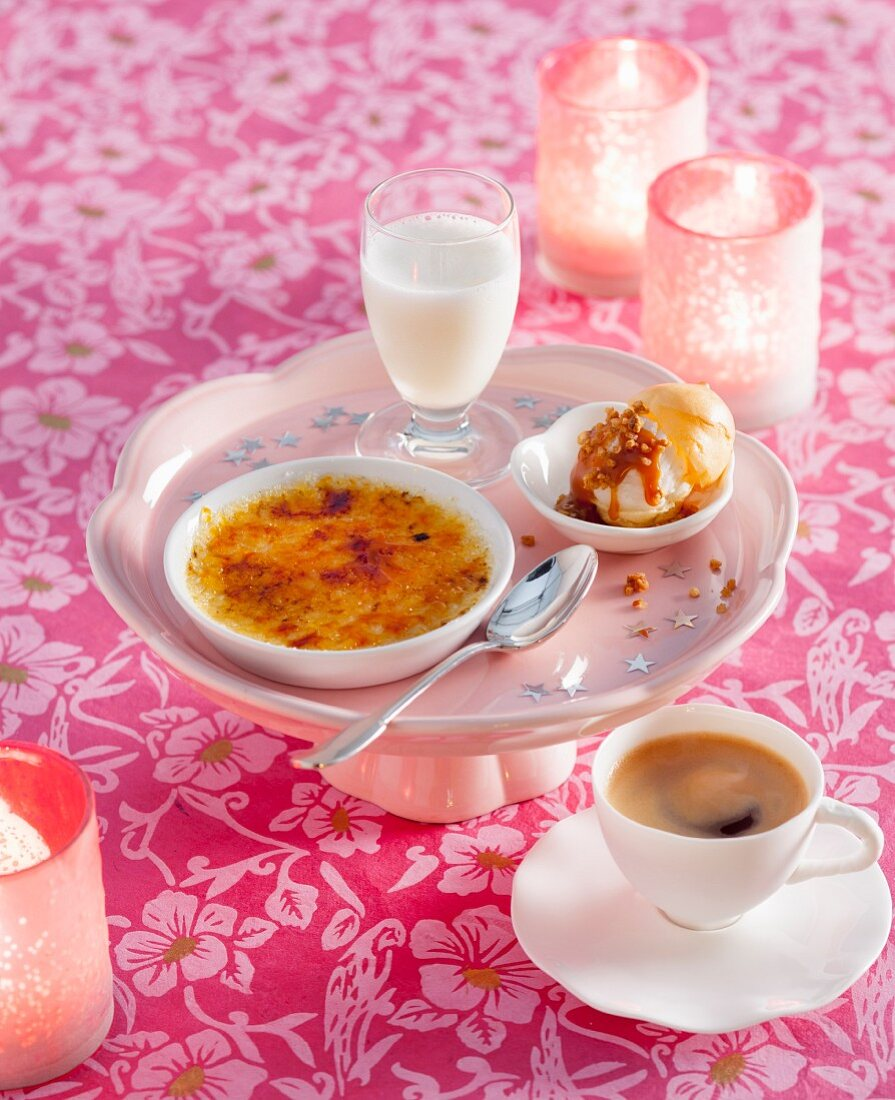 A Christmas dessert platter with crème brûlée, a profiterole with ice cream and a lemon sorbet and Prosecco drink