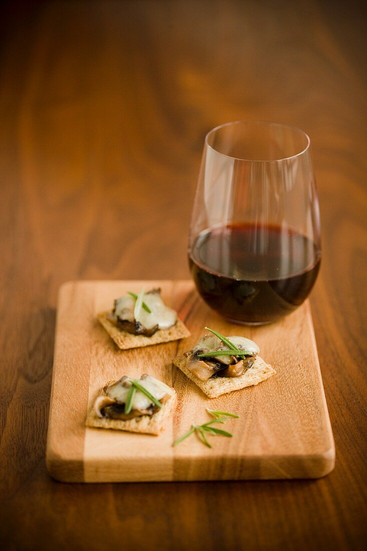 Crackers with mushrooms, cheese and rosemary served with red wine