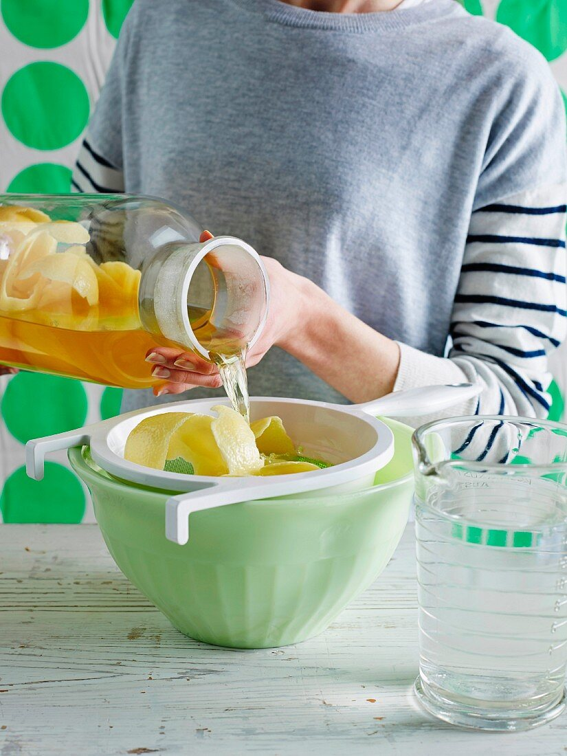 A woman sieving iced tea with lemon peel