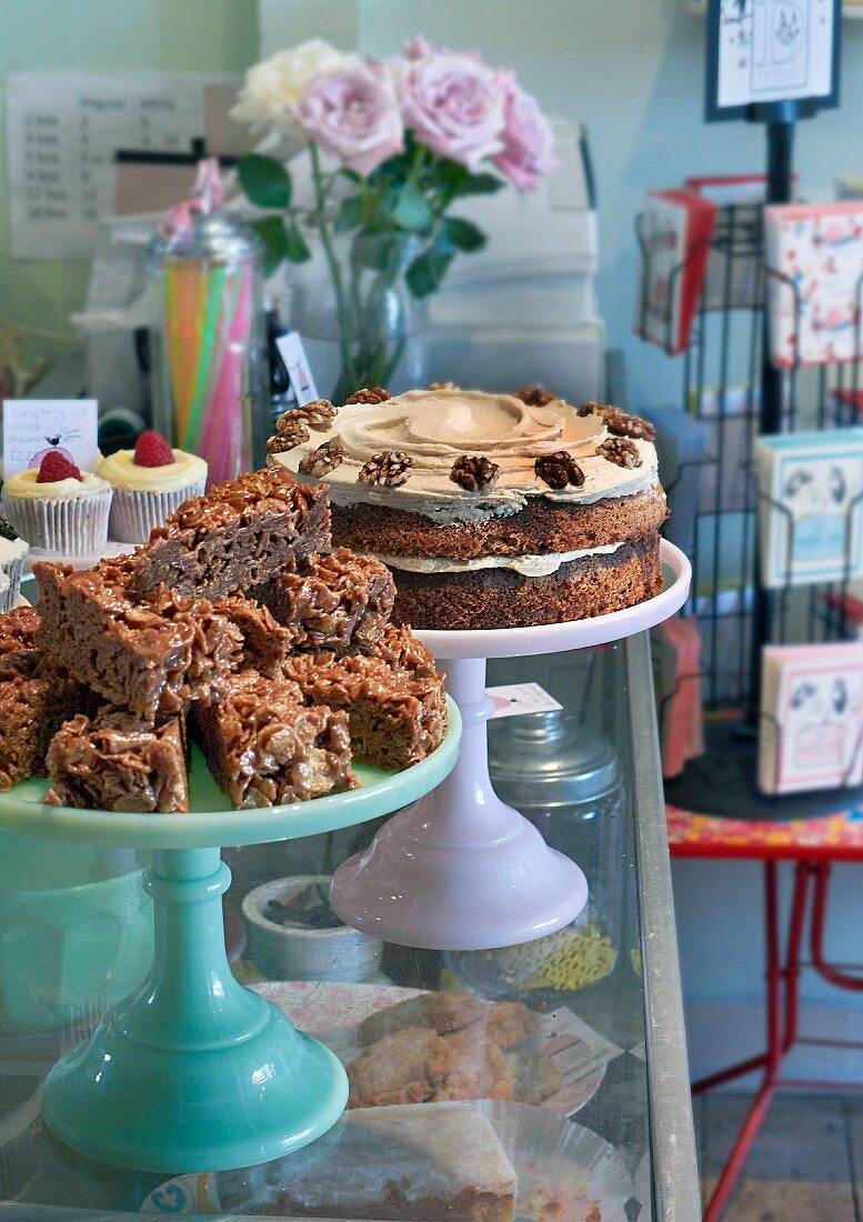 Various cakes and cupcakes on top of a display cabinet in a restaurant