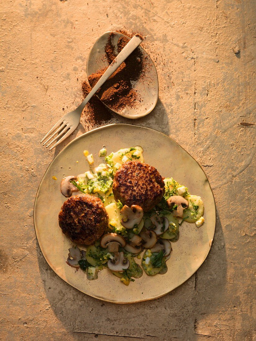 Oriental wild boar burgers with a potato and herb sauce served with salad
