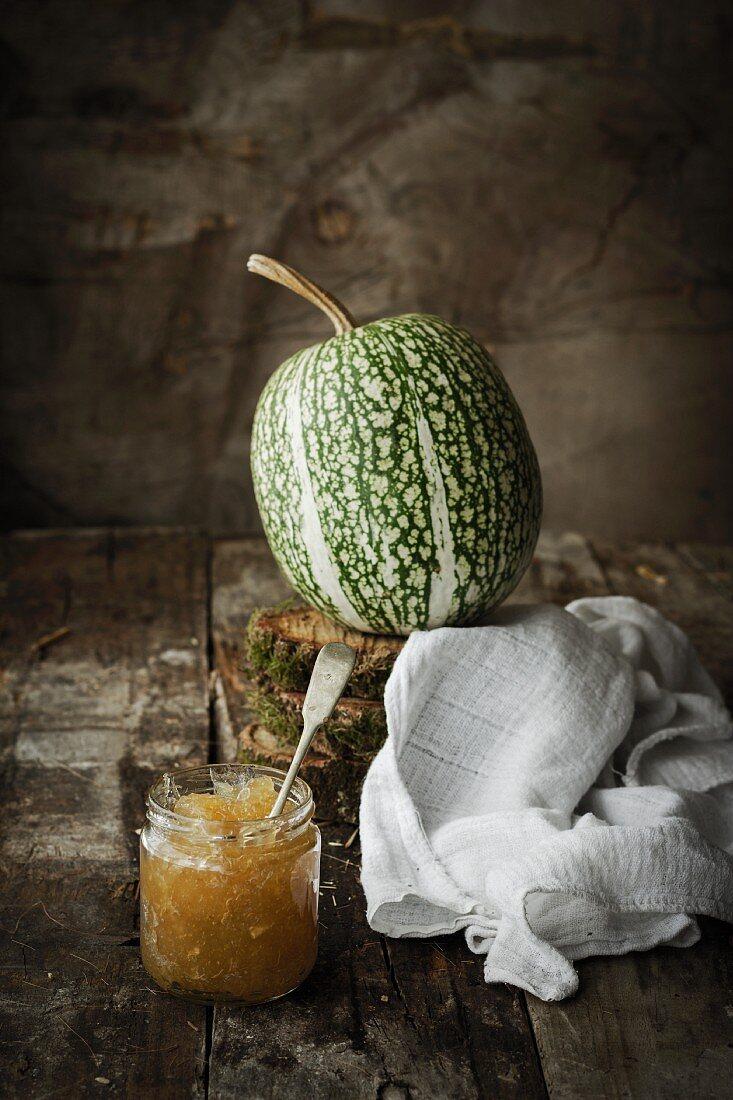 A glass of pumpkin jam with a fresh pumpkin
