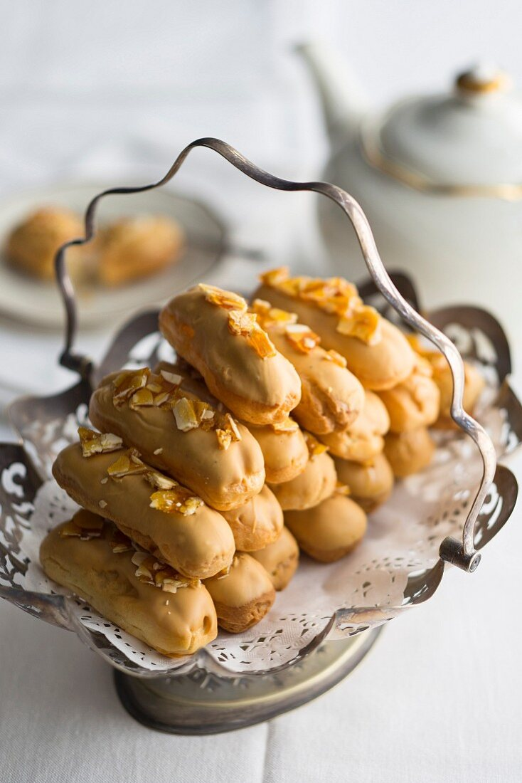 Caramelised white chocolate eclairs with almond milk cream and salted almond brittle served with tea