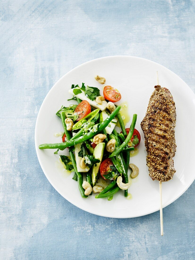 Veal skewer with sesame seeds and a bean salad