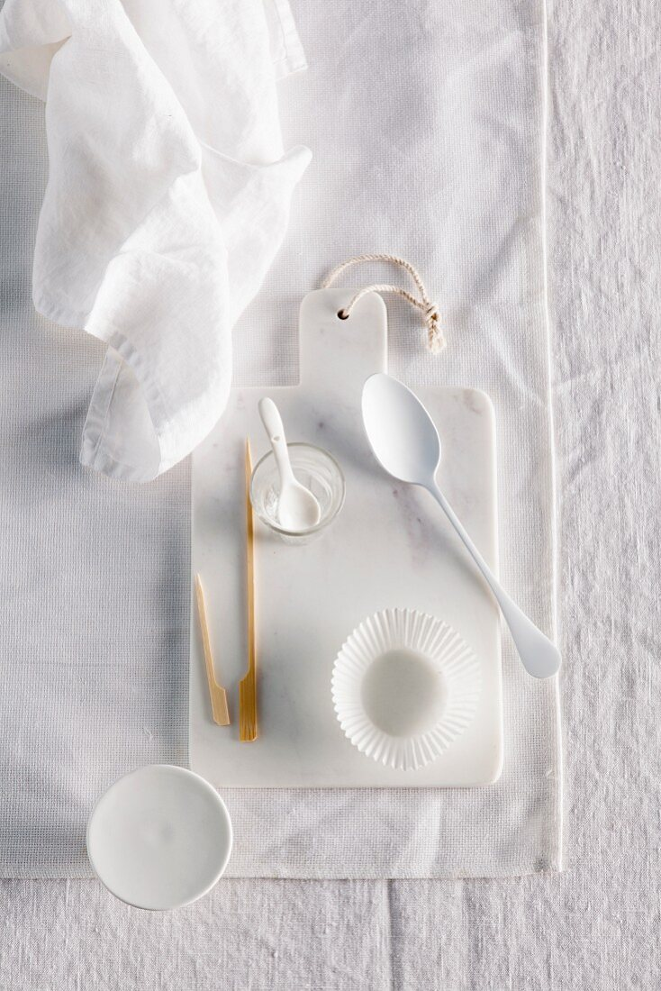 Spoons, paper cases, bowls, wooden skewers and a mini cake stand on a white chopping board on a white surface