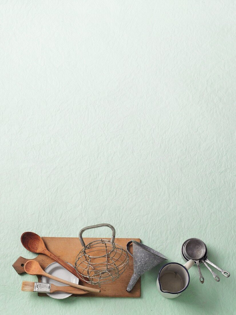 Various kitchen utensils on a pastel green surface