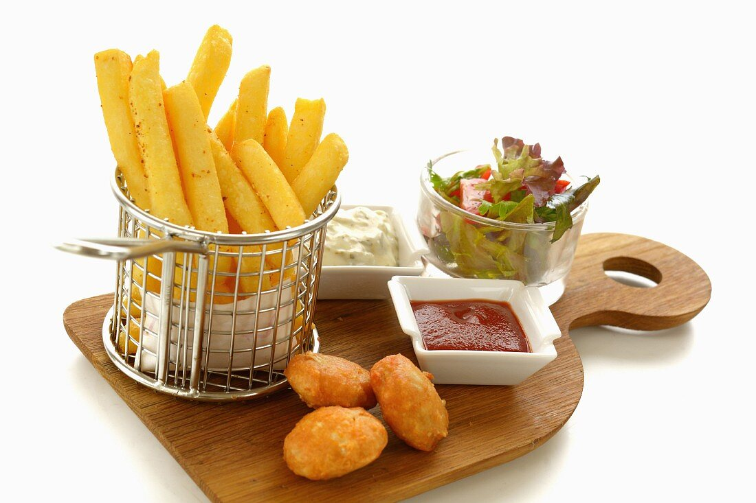 Chicken nuggets with chips, two sauces and a salad