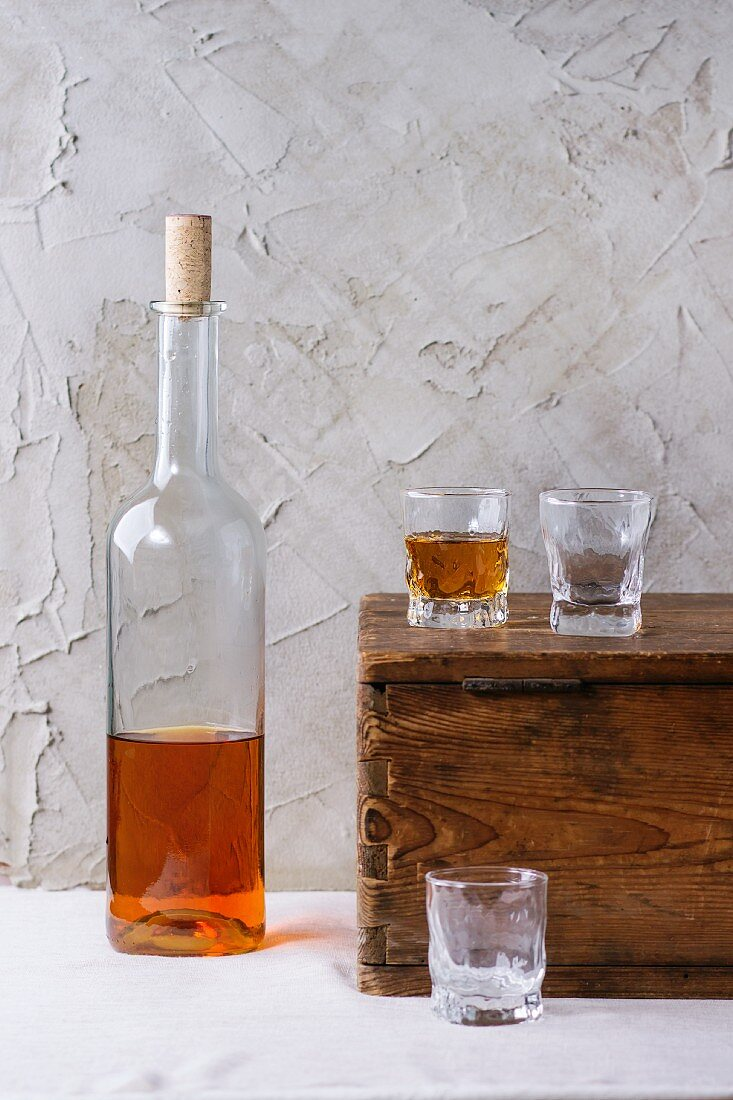 A bottle of rum and three glasses on a wooden chest in front of a plastered wall