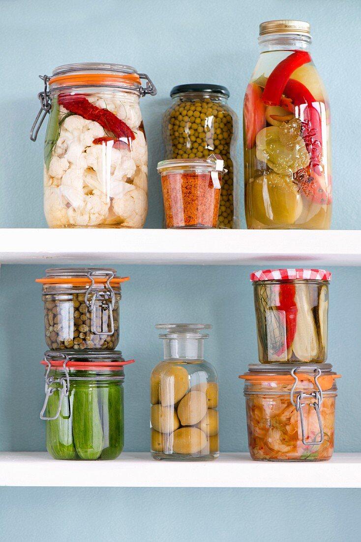 Various jars of preserved vegetables on a shelf