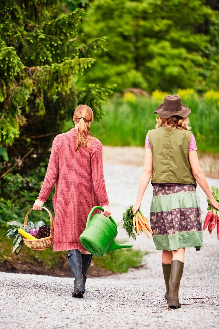 Two women carrying vegetables along a forest road