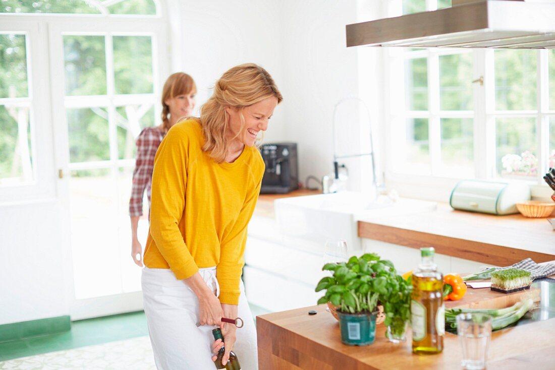 A woman opening a bottle of wine bottle in a kitchen