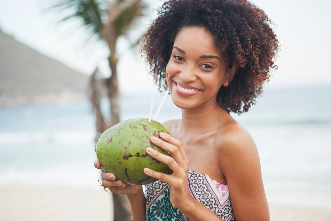 A young South American woman drinking coconut milk on a beach in Rio (Brazil)