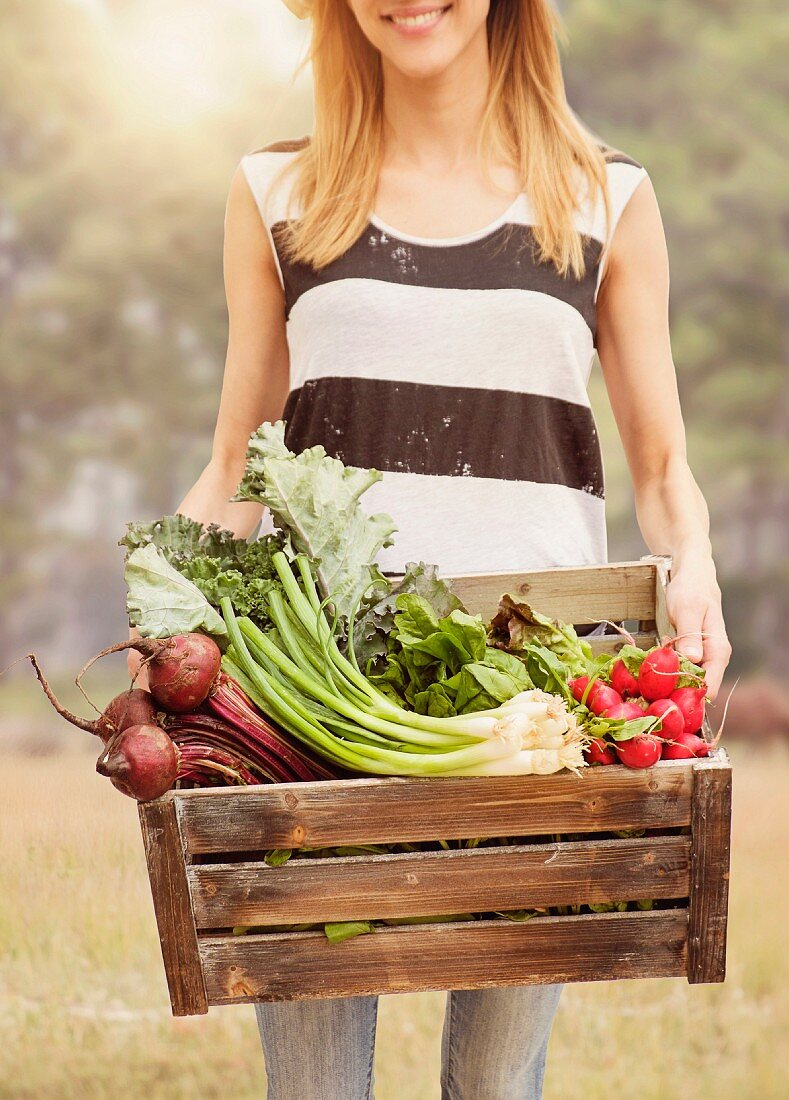 A young woman carrying a wooden crate of fresh garden vegetables