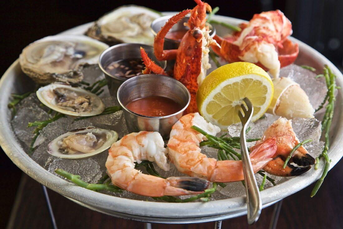 Oysters, prawns and crab with sauces and lemon on ice
