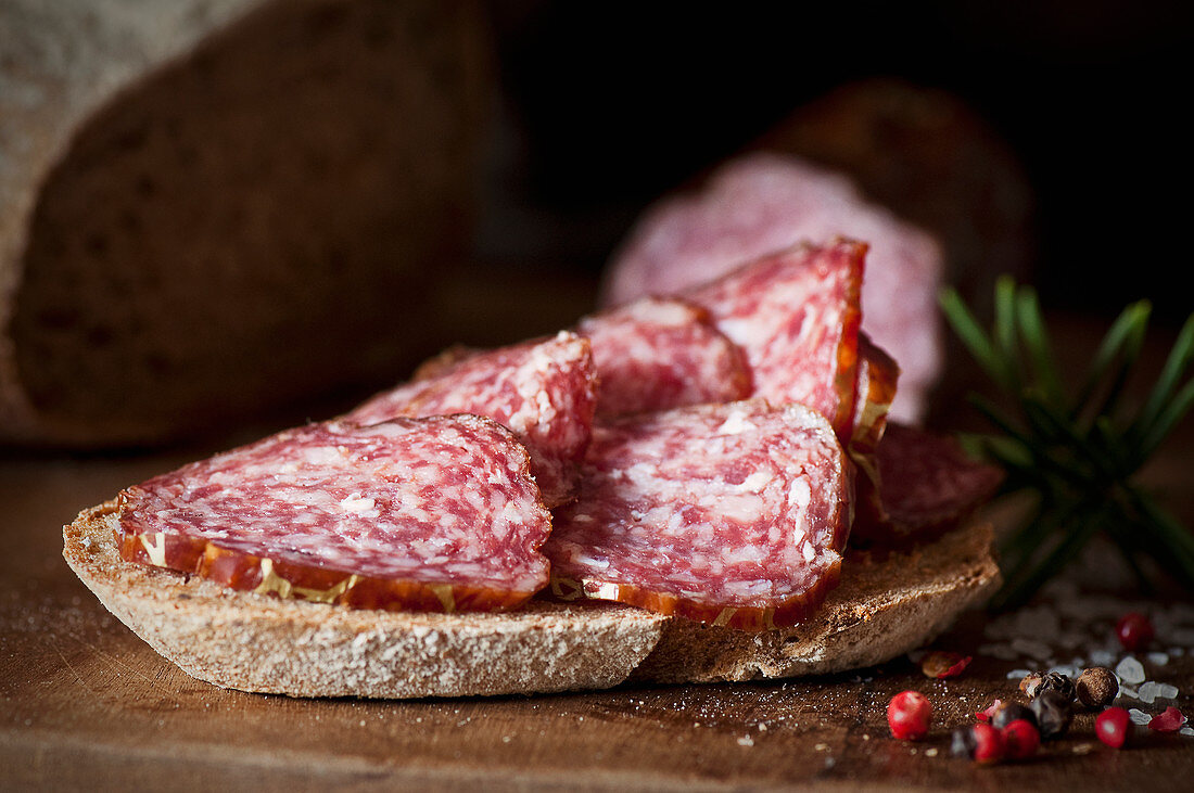 A slice of bread topped with red wine salami