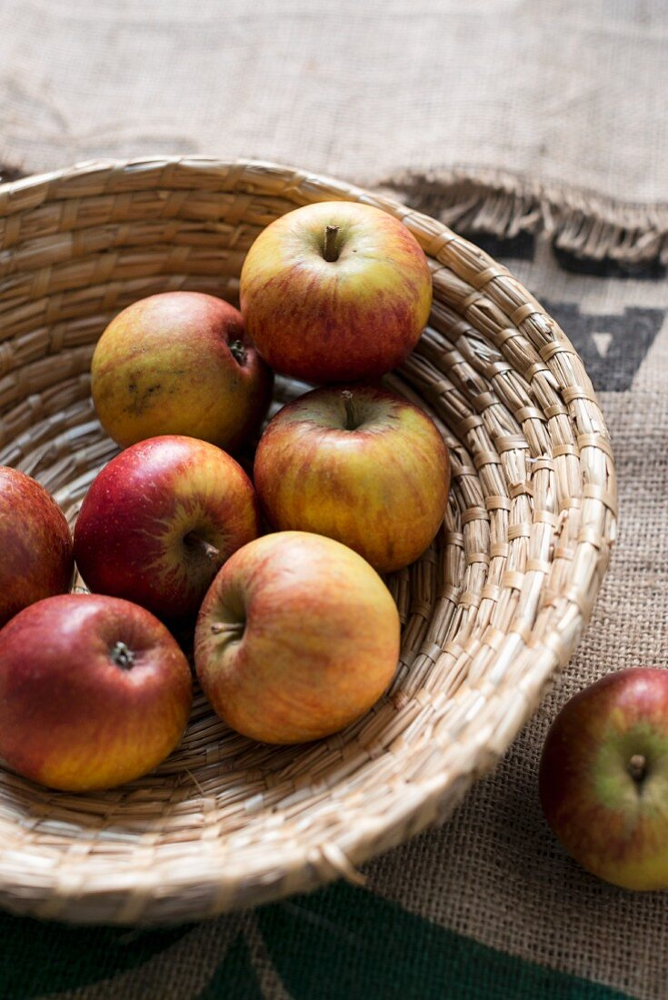 Red and yellow apples in a wicker bowl
