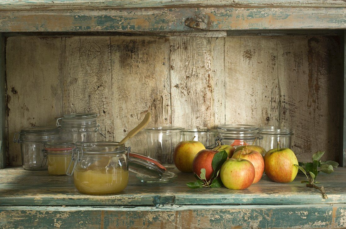 A rustic arrangement of apple compote, preserving jars and fresh apples