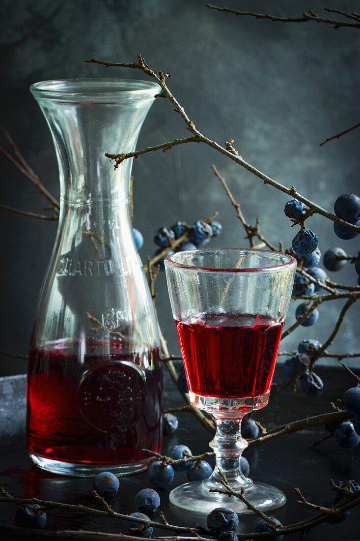 Schlehenwein in Glas und Glaskaraffe vor Schlehenzweig im Hintergrund