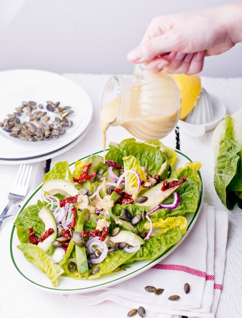 mixed leaf salad with avocado, onions and pumpkin seeds