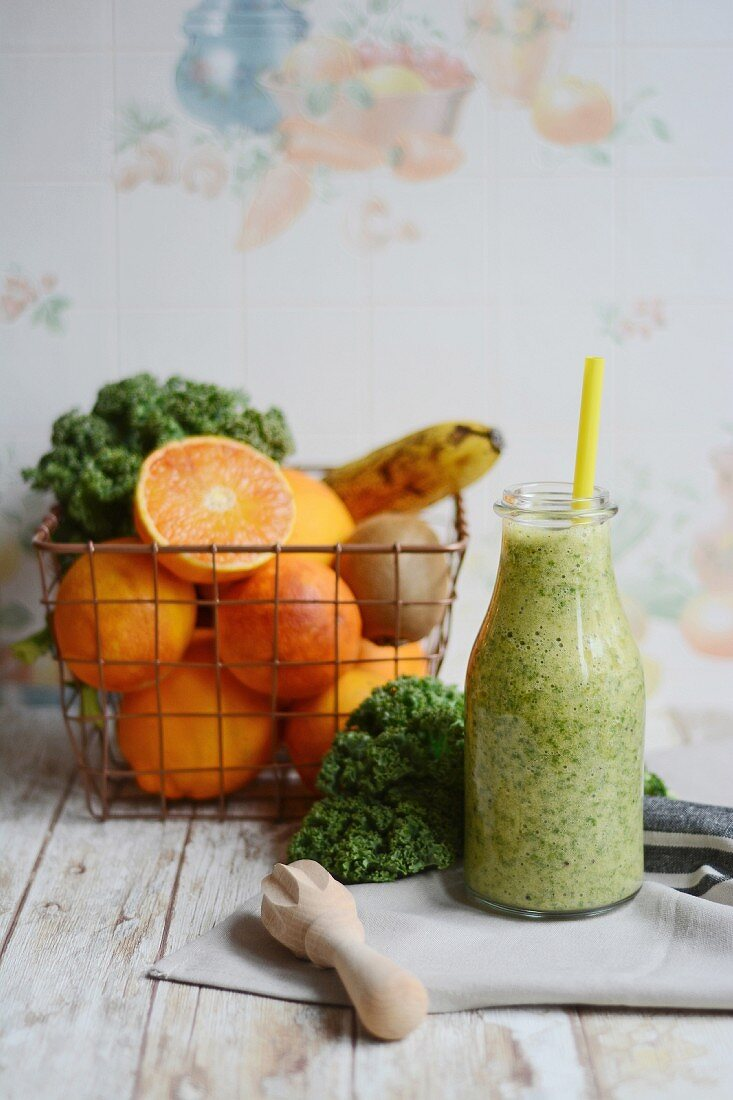 A smoothe made with kale, banana, orange and kiwi