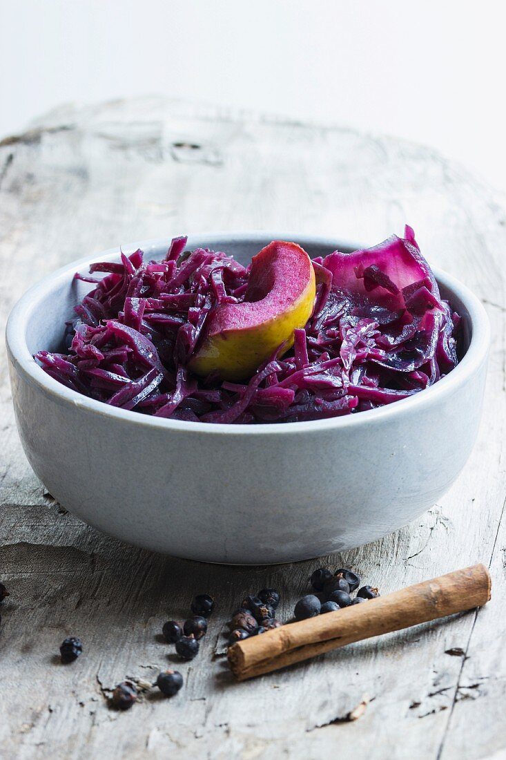 Red cabbage with apple, cinnamon and juniper berries in a grey bowl on a wooden board