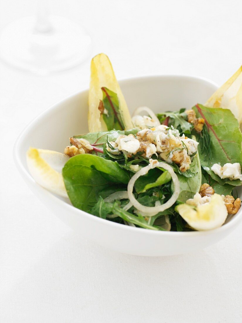 A green salad with nuts, onions and dressing