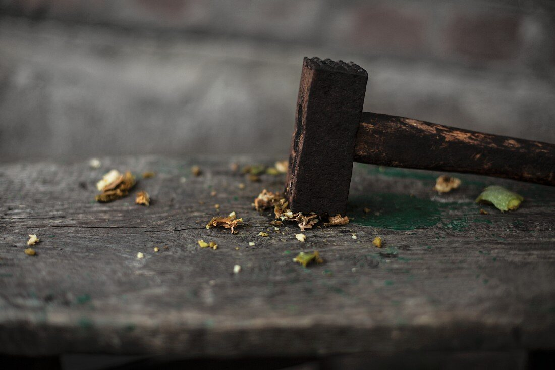 A crushed walnut with a hammer on a wooden table