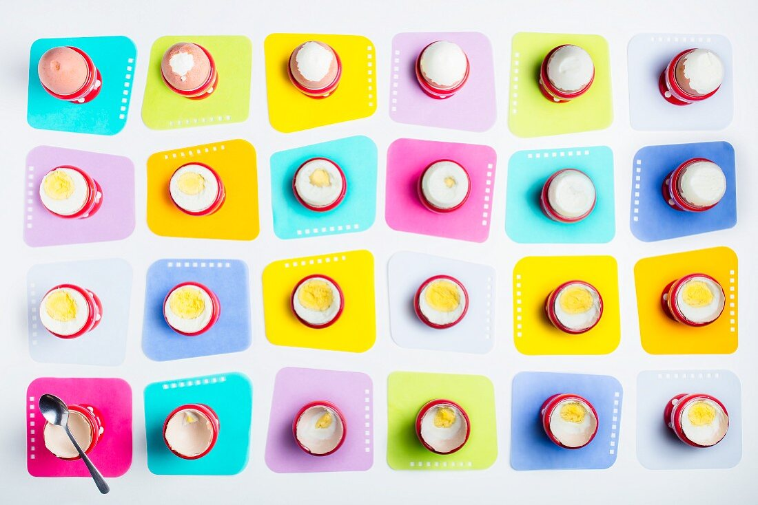 Boiled eggs in egg cups on coloured coasters (seen from above)